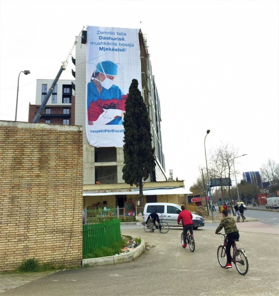 """Street scene in Tirana. Text on transparent: """"Give your heart to love, and for your lungs trust Medicine."""" (Picture: © Cyriakus Bräutigam)"""